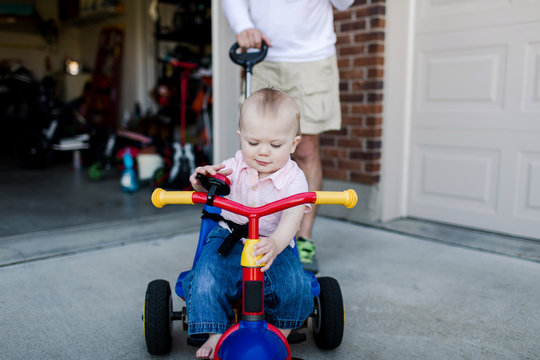 baby being pushed on a tricycle