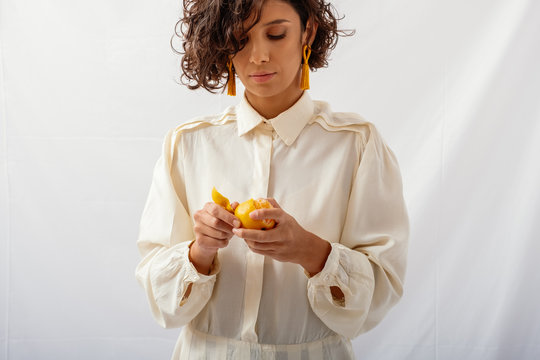 Model Wearing Natural Fabrics And Holding Fruit