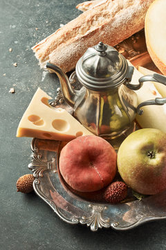 Different juicy fruits, baguette, cheese, teapot in an old metal