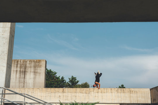 Young hispanic latin break dancer performing a dance pose over architectural structure