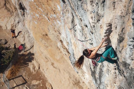 Young climber woman climbing a steep overhanging tufa limestone wall, Oliana, Spain