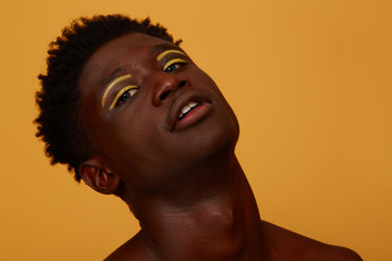 Portrait of young man with yellow makeup