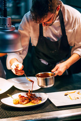 Professional chef pouring sauce on served meat