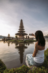 beautiful young woman taking a picture with her mobile phone from ulun danu beratan temple