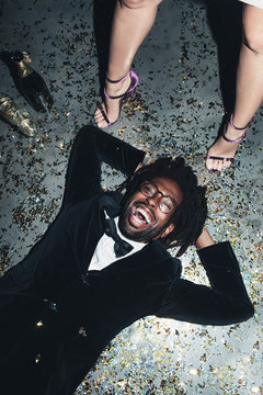 Directly above view of man lying on party floor laughing