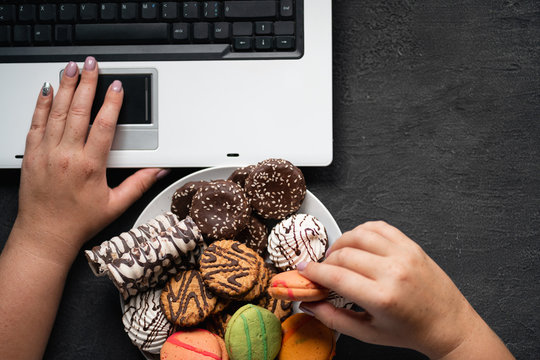 Unhealthy snack at work time. Compulsive indulgence, overeating, stress, high calorie, fattening junk food, weight gain. Woman eating cookies at workplace