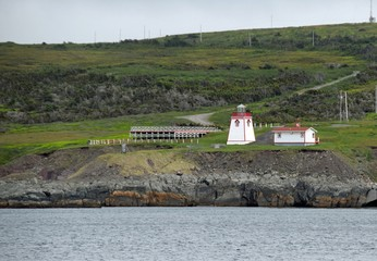 view across the ocean towards the red and white Fortune Head Lighthouse; Burin Peninsula Newfoundland Canada
