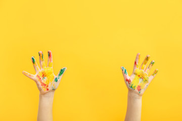 Child's hands in paint on color background