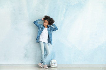 Stylish African-American girl in jeans clothes and with backpack near color wall Wall mural