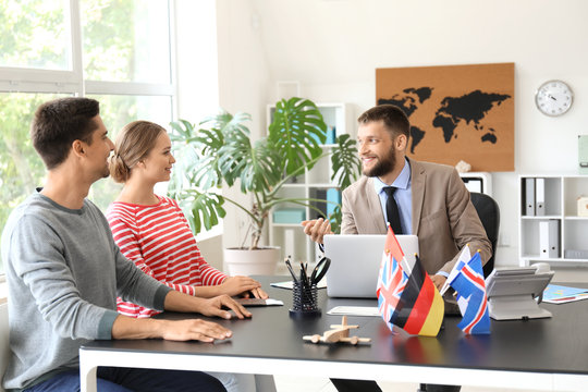 Male travel agent working with young couple in office