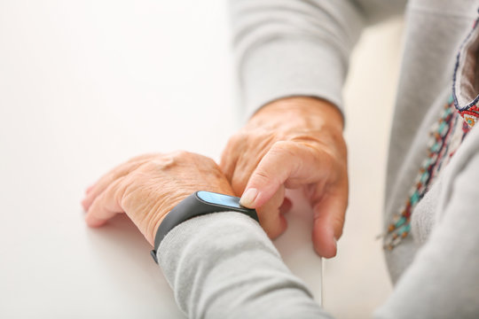 Elderly woman with fitness band checking her pulse, closeup