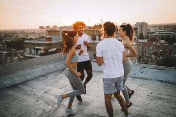 Group of happy fit friends exercising outdoor in city Wall mural