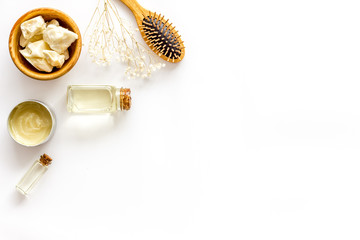 Bottle with jojoba, argan or coconut oil, styling, comb for hair style on white background top view mock up
