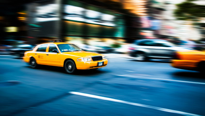 Yellow cab taxi traditional of New York City in fast movement with motion blur panning, in the busy streets of Manhattan, accelerating traffic moves during evening.