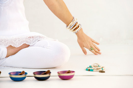 Woman sitting in meditation with sound healing bowls and mala beads.