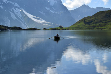 Boat on Trüebsee, Mount Titlis, Switzerland. Calm lake surface wit mountains reflected in the water.