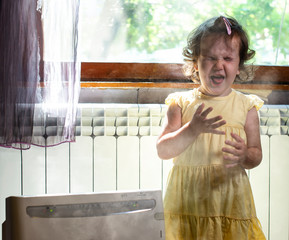 Little girl in a dusty room. Air purifier and coughing kid. Dust in the air.