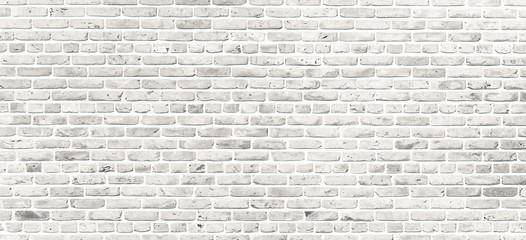 White brick wall. Simple grungy white brick wall with light gray shades pattern surface texture background in wide panorama format. Wall mural