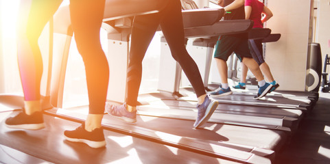 Group of people in sportswear running around on a treadmill. Cardio workout at the gym. Fototapete