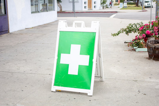 A general white and green cross symbol indicating a nearby marijuana dispensary