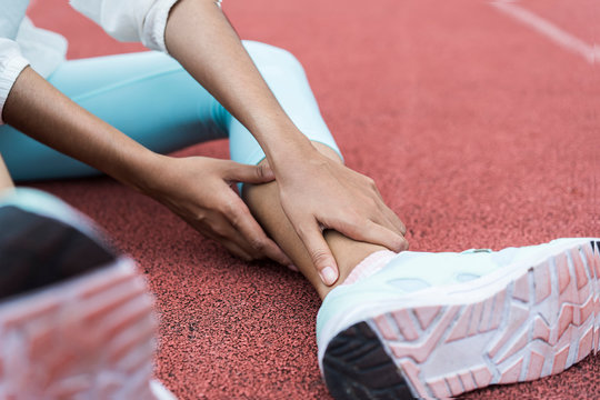 Close up of hand Athletic woman suffering or injury leg after exercise. Asian woman or student has pain in his foot or shin while running track has calf cramp and touching hurt leg or sprained ankle