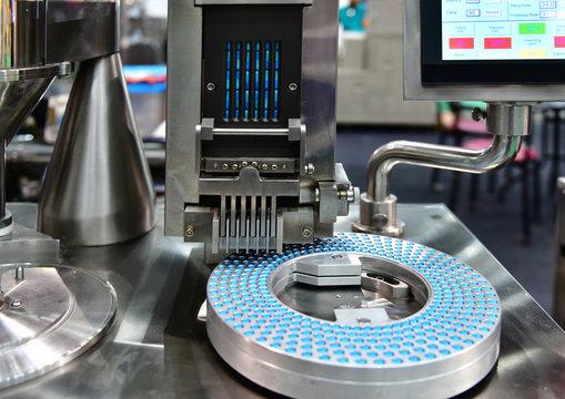 Blue capsule medicine pill production line, Industrial pharmaceutical concept.banner size