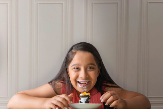 Smiling girl with milk mustache eating a stack of cream biscuit pie