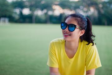 Lovely teen girl street style smiling with sunglasses under sunshine