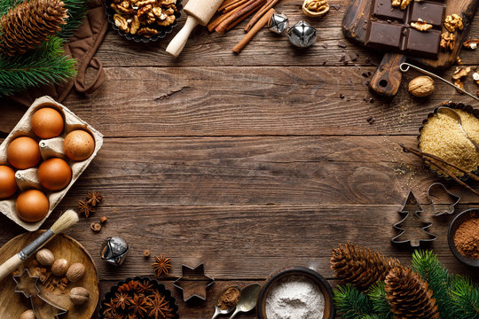 Christmas or new year culinary rustic wooden background with food ingredients for cooking festive dishes, xmas baking. Holiday cooking frame for Noel pastry on wooden table