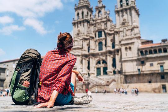 Woman backpacker piligrim siting on the Obradeiro square (plaza) in Santiago de Compostela