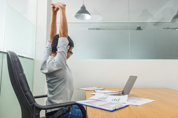 Tired Asian employee stretching in front of computer at office