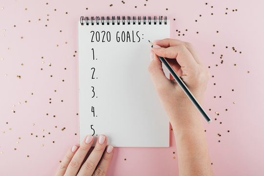 Happy New Year 2020. Woman's hand writing 2020 Goals in notebook decorated with Christmas decorations on the pink background. Top view, flat lay