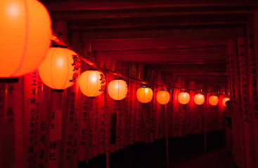 Vermilion torii gates with red lanterns in Kyoto, Japan