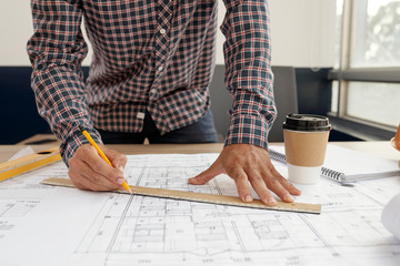 Close-up of young engineer in checked shirt using ruler and drawing the blueprint of new building or house with pencil at office