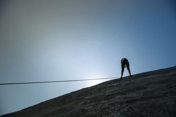 Femme en train d'escalader en contre jour