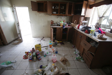 Food and kitchen items are scattered on the kitchen floor of a house seized by authorities in Ciudad Juarez