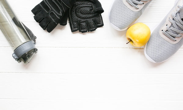 Sport photo. Healthy lifestyle. Bottle for water, apple and leather gloves. Stylish trainers. White wooden background. Perfect flat lay.