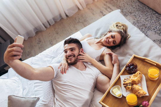 Young happy couple having breakfast in luxury hotel room using smart phone to take selfie photo.