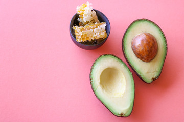 Avocado halves and a small bowl with honeycombs isolated on pink/coral background