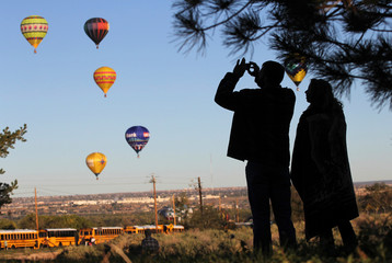 Visitor takes pictures of hot air balloons flying overhead during the 42nd annual Albuquerque International Balloon Fiesta in Albuquerque