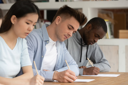 Focused multiethnic young people write passing exam at school