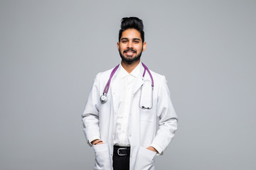Male Indian doctor wearing a white coat and stethoscope isolated on white background.