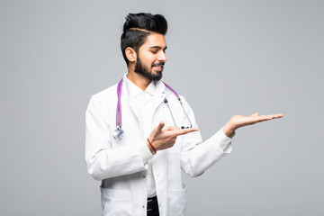 Cheerful indian doctor presenting copyspace next to him with palms isolated on white background