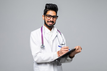 Young indian man doctor with stethoscope over neck holding clipboard isolated on white