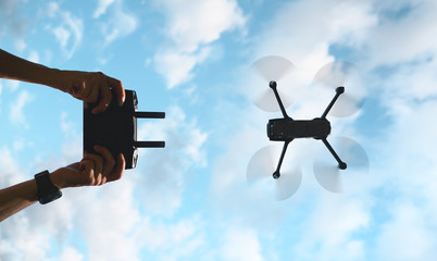 Radio remote control in male hands. Drone silhouette. View from the bottom. Cloudy sky. Wall mural