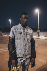 portrait of young black man standing outdoor in parking space