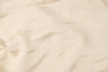 Soft smooth beige silk fabric background. Fabric texture.