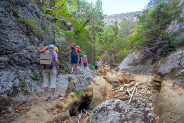 Tourists with backpacks travel in mountains. Crimea