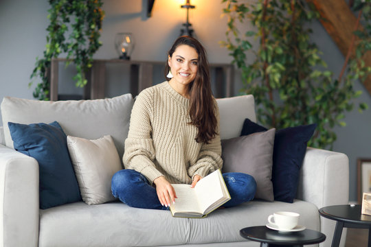 Young happy brunette woman with book wearing sweater