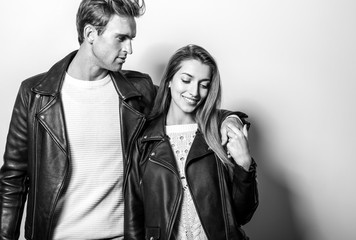 Young beautiful couple in black leather jackets. Black-white portrait. Wall mural